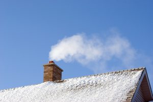 White smoke comes out of a house's chimney on a winter day.