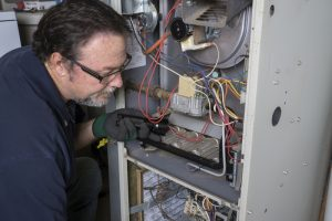 technician-looking-over-gas-furnace