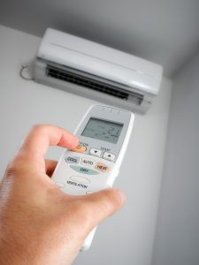 closeup-view-of-hand-turning-on-ductless-air-handler-remotely
