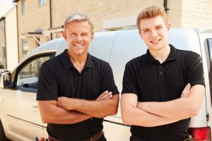 young-and-middle-aged-hvac-technicians-standing-in-front-of-van