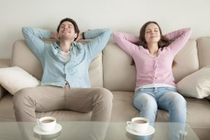 young-couple-sitting-in-home-smiling