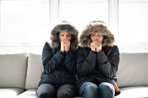 couple-sitting-with-parkas-on-in-living-room