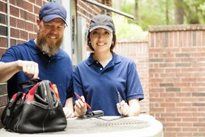 male-and-female-technician-standing-over-outside-ac-unit-with-tool-bag-and-tools