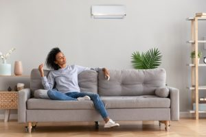 woman-in-living-room-enjoying-cool-breeze-from-ductless-air-conditioner