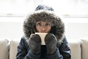 woman-inside-with-parka-on-drinking-out-of-mug