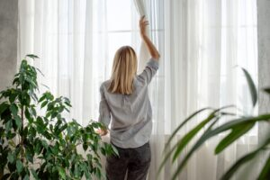 woman-opening-curtains-in-home