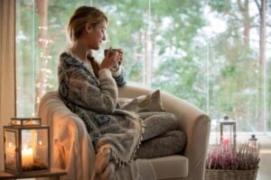 woman-sitting-on-comfy-chair-sipping-out-of-mug